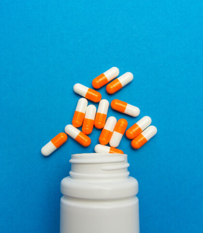 A white plastic cylindrical medical pill bottle with the grooves of a screw top at the neck of the vessel lies on its side. Between 10 and 20 oblong orange and white pill capsules are arranged as if they've spilled out of the open bottle. Bottle and pills alike are on a light blue background which takes up the entire frame of the photo