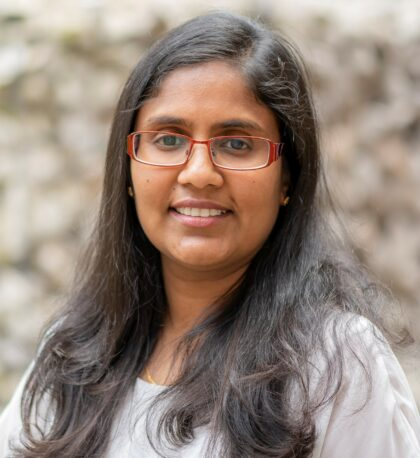 Close cropped head and shoulders profile picture of Dr. Monalie Bandulasena. She is a south asian woman descended woman in her late 30s with shoulder length dark hair and red medium width framed glasses wearing a light grey blouse