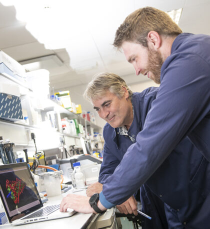 Picture of two of the NanoSyrinx founders. Both are white men, one in his fifties the other in his thirties. They are in a laboratory setting, wearing blue overalls and leaning on a work bench to look at a laptop screen which displays a 3d graphic