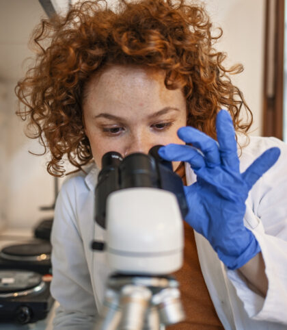 A woman scientist looks into a microscope. She is in a research setting with scales on the counter next to her and she looks into a white microscope with numerous black lenses one of which she is adjusting with a blue plastic goloved hand. The woman is of a white ethnicity, in her 30s, has a small just about visible nose ring, curly red hair and freckles, she wear a white lab coat