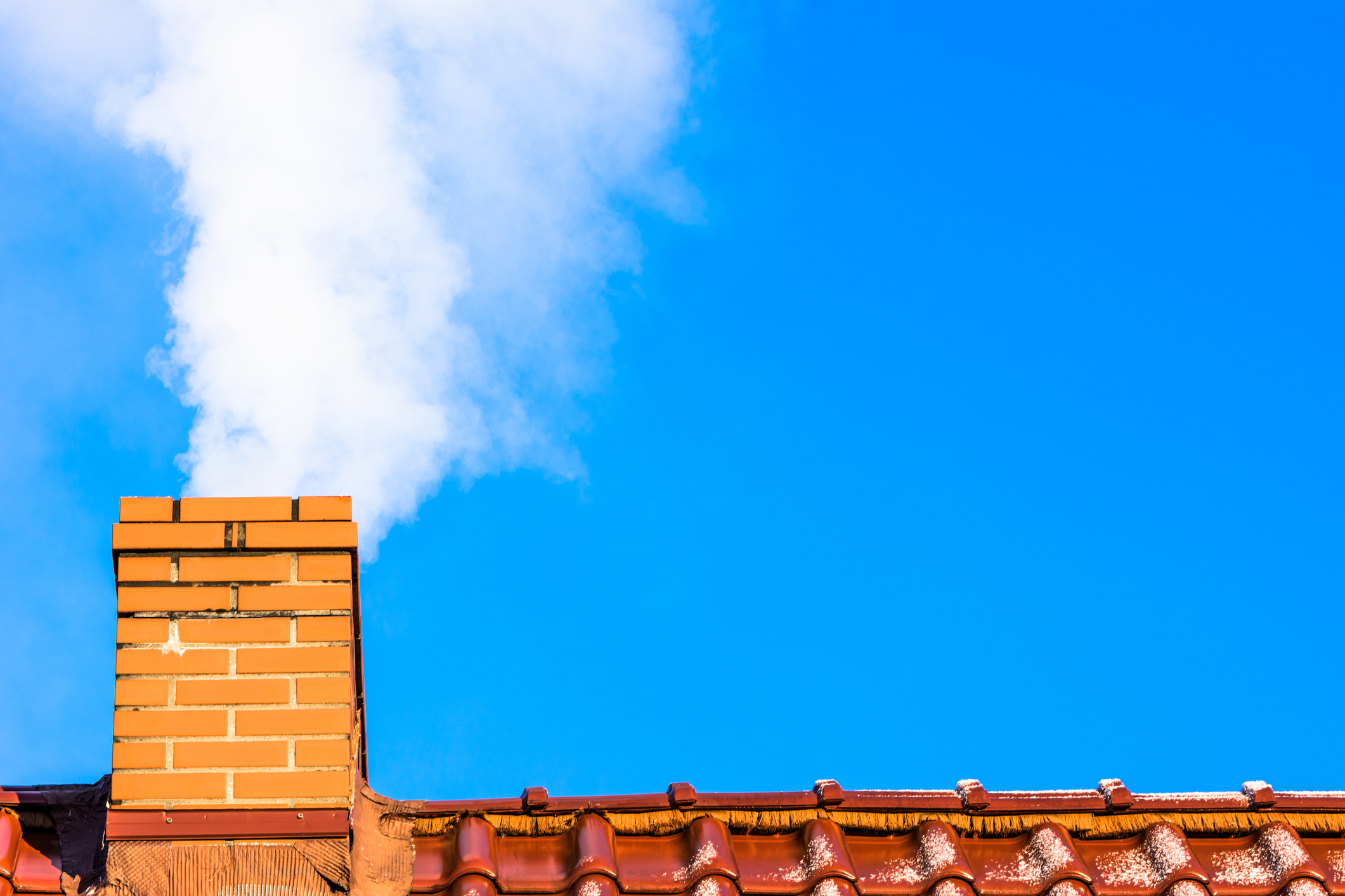 Modern house roof with chimney smoke, air pollution and smog in winter
